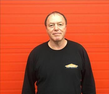 Front photo of Shane in a black SERVPRO shirt with an orange backdrop