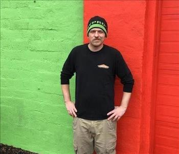 A male SERVPRO employee standing in front of a brick building that is orange and green.