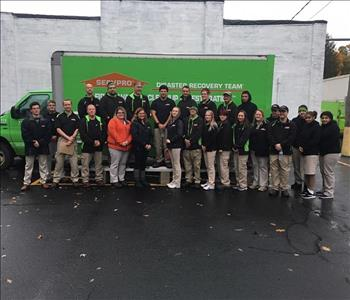 A group of SERVPRO Employees standing in front of a SERVPRO vehicle.