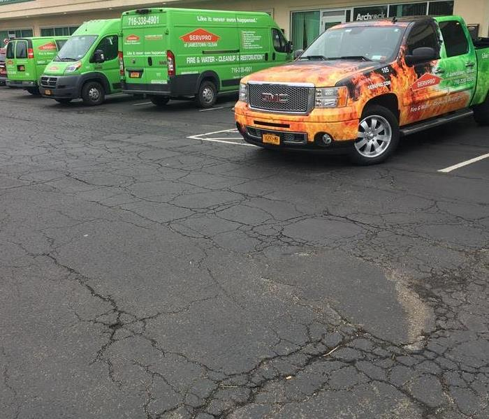 Four SERVPRO vehicles parked in a parking lot.