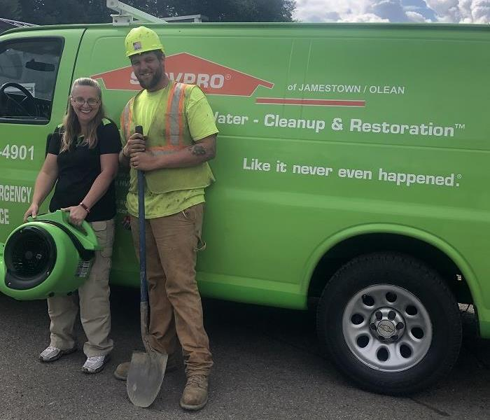 SERVPRO van with man and woman standing beside it