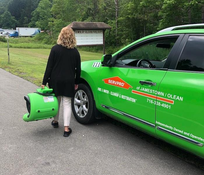 female carrying a green air mover down a street next to a green SERVPRO car
